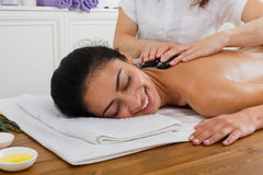 Beautician make stone massage spa for woman at wellness center. Black marble stone back massage in spa. Female beautician doctor with patient in wellness center Stock Photography
