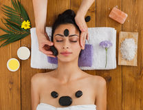 Beautician make stone massage spa for woman at wellness center. Black marble stone face massage in aroma spa. Beautician with female patient in wellness center Stock Photography