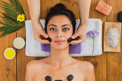 Beautician make stone massage spa for woman at wellness center. Black marble stone face massage in aroma spa. Beautician with female patient in wellness center Stock Photos
