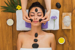 Beautician make stone massage spa for woman at wellness center. Black marble stone face massage in aroma spa. Beautician with female patient in wellness center Royalty Free Stock Images