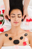 Beautician make stone massage spa for woman at wellness center. Black marble stone face massage in spa, top view. Female patient in wellness center. Professional Stock Photography