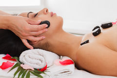 Beautician make stone massage spa for woman at wellness center. Black marble stone massage in spa. Female beautician doctor with patient in wellness center Stock Image