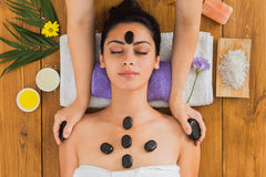Beautician make stone massage spa for woman at wellness center. Black marble stone massage in spa. Beautician with female patient in wellness center Stock Image