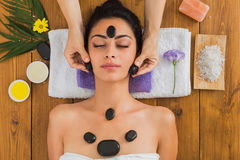 Beautician make stone massage spa for woman at wellness center. Black marble stone massage in spa. Beautician with female patient in wellness center Royalty Free Stock Photo