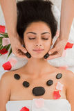 Beautician make stone massage spa for woman at wellness center. Black marble stone massage in spa. Female patient in wellness center. Professional massagist make Stock Photography