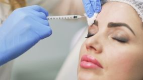 Beautician makes botox injection in the forehead. Beautician makes a facial botox injections with syringe. Doctor patient`s forehead with hyaluronic acid. Young