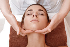 Beautician makes face massage Stock Images