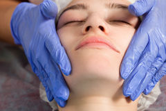 Beautician makes a facial massage royalty free stock photos