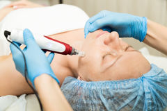 Beautician makes fractional mesotherapy to young woman. The cosmetic procedures for the face. Beauty treatments in the Stock Photo