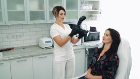 Beautician makes photo on camera of patient before cosmetic procedure, slow motion. Young woman on reception at cosmetologist stock video