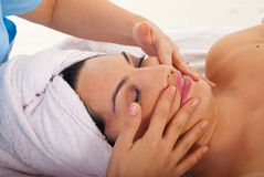 Beautician massaging woman face Stock Photo