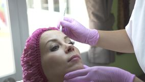 Beautician ocechowania twarz dla kosmetycznego zastrzyka w medycznej klinice Kobieta w piękno klinice Twarzy opieka i anty starze zbiory