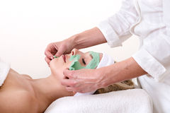 Beautician peeling off a green thalasso beauty facial mask. Beautician peeling off the green beauty facial mask on a laying and relaxed beautiful blond women Royalty Free Stock Image