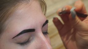 Beautician performs eyebrow correction for a young woman. Eyebrow care stock footage