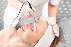 Facial skin care. Woman in a beauty salon. The beautician performs a firming treatment using a specialized machine Royalty Free Stock Image