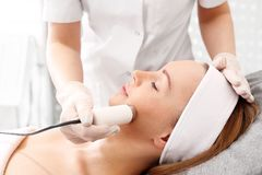 Iontophoresis. Aesthetic medicine treatment. The beautician performs a firming treatment using a specialized machine Royalty Free Stock Photos