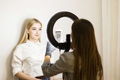 Beautician photographs his work on a mobile phone. Two girls in a beauty salon. Ring lamp for makeup artists. Face care stock images