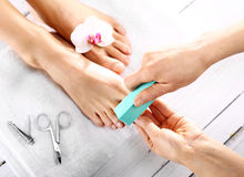 Beautician polishing nails, pedicure. Foot care treatment and nail, the woman at the beautician for pedicure Royalty Free Stock Image