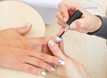 Beautician polishing woman nails Royalty Free Stock Photos
