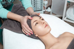 Beautician prepares patient for Spa procedures in Spa salon. young woman with towel on head Royalty Free Stock Photo