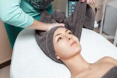 Beautician prepares patient for Spa procedures in Spa salon. young woman with towel on head Stock Photos