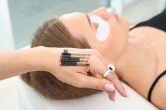 Beautician preparing for eyelash extensions procedure. Closeup stock images