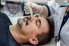 Beautician procedure cleansing face men. Beautician procedure cleansing face of a men royalty free stock photo