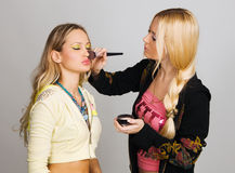 Beautician profesional que aplica maquillaje imagenes de archivo