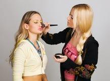 Beautician professionale che applica trucco immagini stock