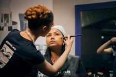 Beautician providing face makeup at beauty expo Royalty Free Stock Photography