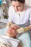 Beautician przygotowywa twarzy dziewczyn śmietanki anastetyka Zdjęcie Royalty Free