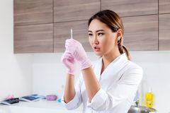 Beautician pushes a syringe to inject Botox royalty free stock images