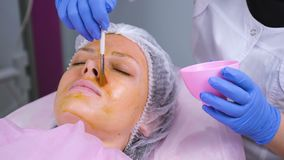 Beautician puts chemical peeling of the woman`s face with brush. Cleaning the face skin and lightening freckles skin. Beautician puts chemical peeling of the stock video