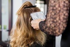 Beautician Putting Foils In Female Client's Hair. Cropped image of beautician putting foils in female client's hair at salon Royalty Free Stock Image