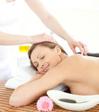 Beautician putting stones on a woman's back Royalty Free Stock Images