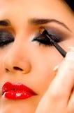 Beautician que aplica la sombra de ojo en el ojo de la mujer Fotografía de archivo libre de regalías