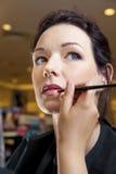Beautician que usa el cepillo del labio Foto de archivo