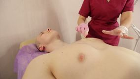 Beautician removes hair from the mans chest with sugar paste. Sugaring. Woman beautician puts a thick sugar paste on the mans chest making him hair removal. A stock video