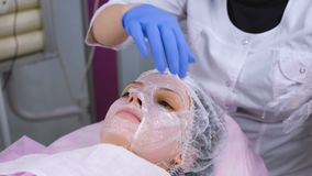 Beautician removes towel from woman`s face. Cosmetologist removes a plastic film from the moisturizing mask on the woman. `s face stock footage