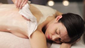Beautician removing cream from woman back at spa stock footage
