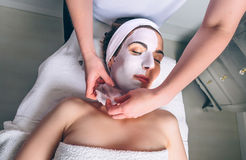 Beautician removing facial mask to woman in spa Stock Photography