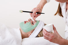 Beautician retouching a blond woman thalasso facial mask. Royalty Free Stock Photography