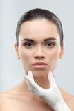 Beautician in rubber gloves touching face of young. Beautician in white rubber gloves touching face of young beautiful woman. Plastic surgery. Close up portrait Royalty Free Stock Photography