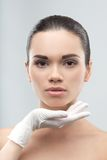 Beautician in rubber gloves touching face of young Royalty Free Stock Photos