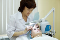 Beautician in salon cleans skin of woman. Royalty Free Stock Images