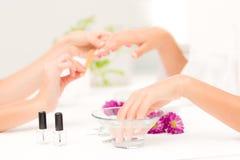 Beautician που αρχειοθετεί τα θηλυκά καρφιά πελατών στο σαλόνι ομορφιάς SPA Στοκ Εικόνες
