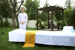 Beautician standing by massage table Royalty Free Stock Photography