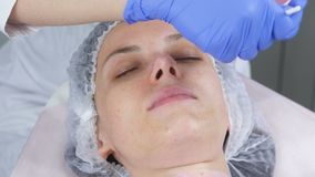 Beautician stawia maskę na kobiety twarzy z muśnięciem Ręki cosmetologist w błękitnych gumowych rękawiczkach facial zbiory