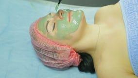 Beautician stosuje kosmetyczną maskę szara glina z muśnięciem na twarzy kobieta zbiory wideo