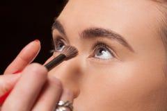 Beautician stosuje kosmetyki na potomstwo modelu zdjęcie stock